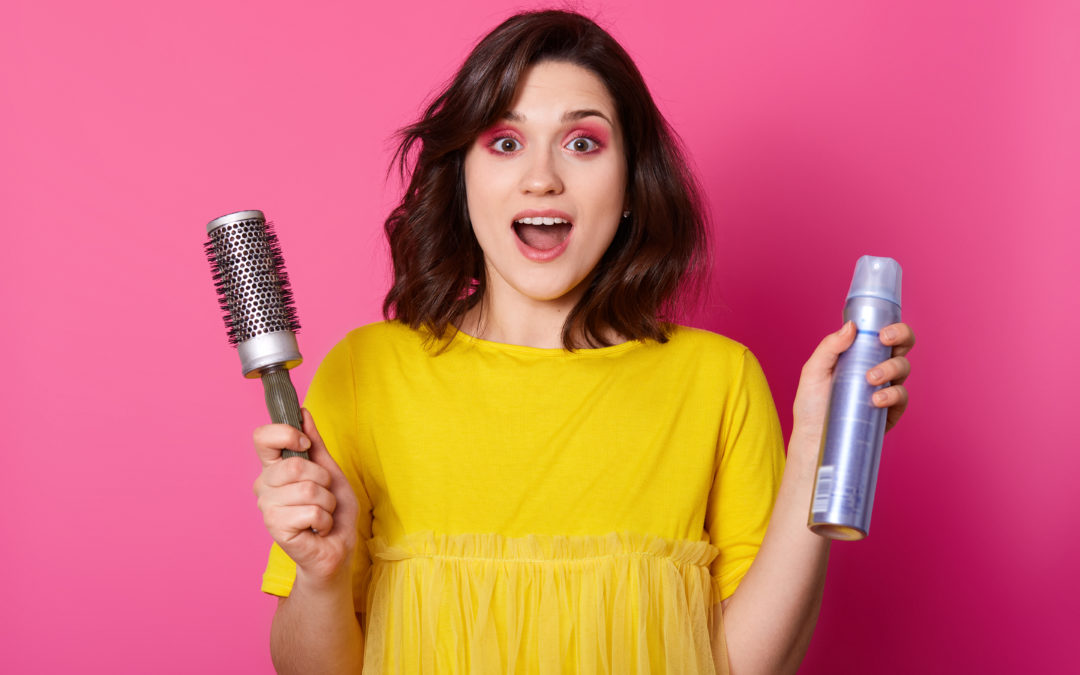 woman holding can of hair spray and a brush